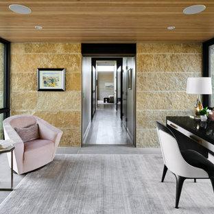 Inspiration för små moderna hemmabibliotek, med kalkstensgolv, ett fristående skrivbord, bruna väggar och grått golv