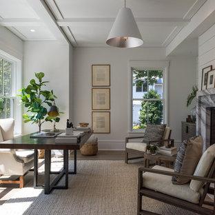Идея дизайна: рабочее место в стиле современная классика с белыми стенами, паркетным полом среднего тона, фасадом камина из камня, отдельно стоящим рабочим столом, коричневым полом и стандартным камином