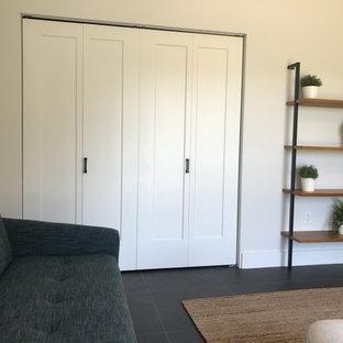 タンパの中くらいのミッドセンチュリースタイルのおしゃれな書斎 (白い壁、スレートの床、暖炉なし、自立型机、黒い床) の写真
