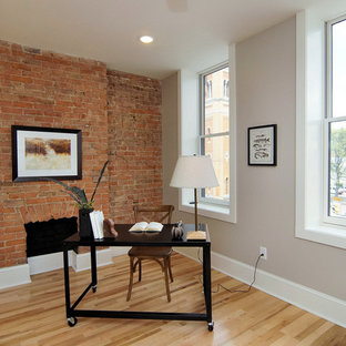 Cette image montre un grand bureau urbain avec un mur gris, un sol en bois clair, un bureau indépendant, une cheminée standard, un manteau de cheminée en brique et un sol beige.