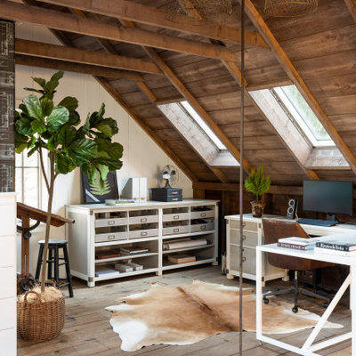 Large farmhouse freestanding desk light wood floor and brown floor study room photo in Boston with white walls