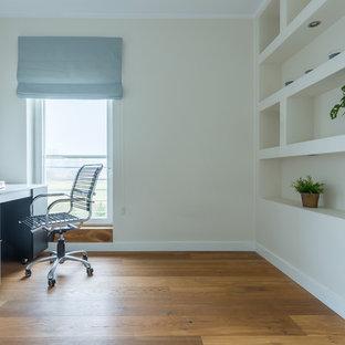 Foto di un ufficio con pareti bianche, parquet chiaro, scrivania autoportante e pavimento giallo