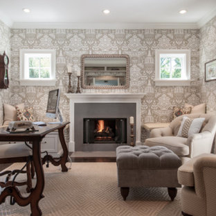 Medium sized traditional home office and library in St Louis with beige walls, dark hardwood flooring, a standard fireplace, a metal fireplace surround, a freestanding desk and brown floors.