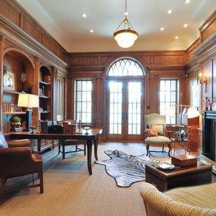 Klassisk inredning av ett stort hemmabibliotek, med bruna väggar, mellanmörkt trägolv, en standard öppen spis, ett fristående skrivbord och en spiselkrans i trä