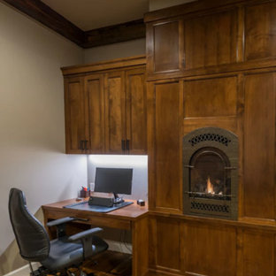Photo of a small rustic study in Other with grey walls, dark hardwood flooring, a wood burning stove, a metal fireplace surround, a built-in desk and brown floors.
