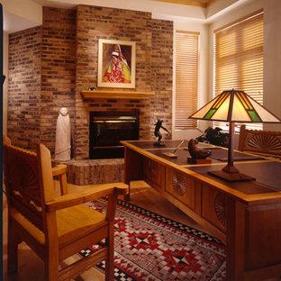Imagen de despacho de estilo americano, de tamaño medio, con paredes multicolor, suelo de madera en tonos medios, chimenea tradicional, marco de chimenea de ladrillo, escritorio independiente y suelo marrón