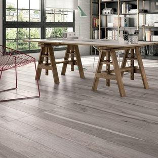 Mittelgroßes Industrial Arbeitszimmer mit Studio, grauer Wandfarbe, braunem Holzboden und freistehendem Schreibtisch in New York