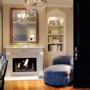 На фото: домашняя библиотека среднего размера в классическом стиле с белыми стенами, паркетным полом среднего тона, стандартным камином, фасадом камина из штукатурки, отдельно стоящим рабочим столом и коричневым полом с