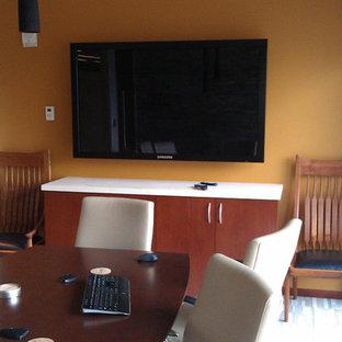 Foto di un grande atelier con pareti arancioni e scrivania autoportante