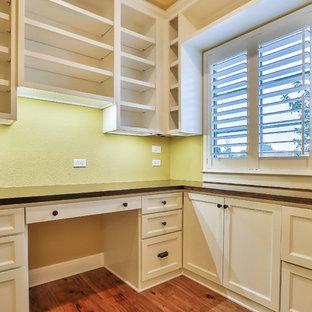 Esempio di un piccolo ufficio chic con pareti gialle, pavimento in legno massello medio, nessun camino, scrivania incassata e pavimento marrone