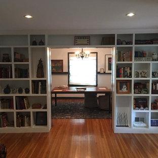 Foto de despacho clásico, de tamaño medio, sin chimenea, con paredes blancas, suelo de madera clara y escritorio independiente