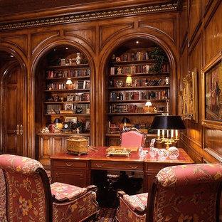 Großes Klassisches Arbeitszimmer ohne Kamin mit dunklem Holzboden, freistehendem Schreibtisch und brauner Wandfarbe in Salt Lake City