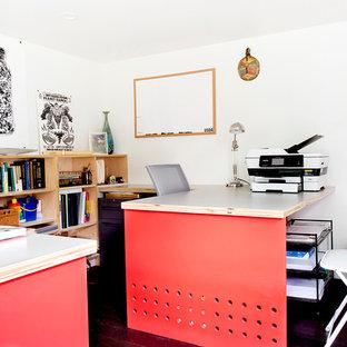 Inspiration för ett litet funkis hemmabibliotek, med vita väggar, mörkt trägolv och ett inbyggt skrivbord