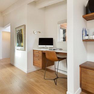 Immagine di uno studio minimalista con pareti bianche, parquet chiaro, cornice del camino in intonaco e scrivania incassata