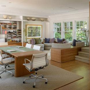 Inspiration för mycket stora moderna hemmabibliotek, med mellanmörkt trägolv, vita väggar och ett fristående skrivbord
