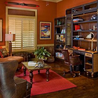 Großes Kolonialstil Lesezimmer mit roter Wandfarbe, dunklem Holzboden, freistehendem Schreibtisch und braunem Boden in Phoenix