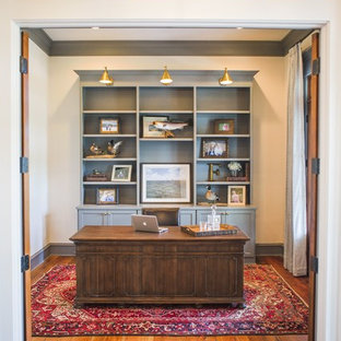 Study room - large traditional freestanding desk medium tone wood floor and brown floor study room idea in Houston with white walls and no fireplace