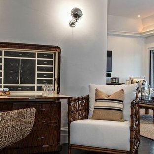 Immagine di un piccolo studio tropicale con pareti grigie, parquet scuro, scrivania autoportante e pavimento marrone
