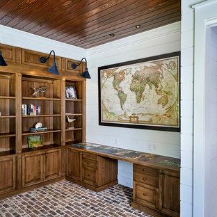 Inredning av ett lantligt stort hemmabibliotek, med vita väggar, tegelgolv, ett inbyggt skrivbord och brunt golv