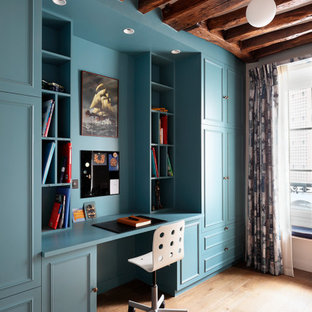 This is an example of an eclectic home office and library in London with medium hardwood flooring, a built-in desk and brown floors.