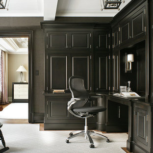 Example of a classic built-in desk medium tone wood floor home office design in New York with gray walls