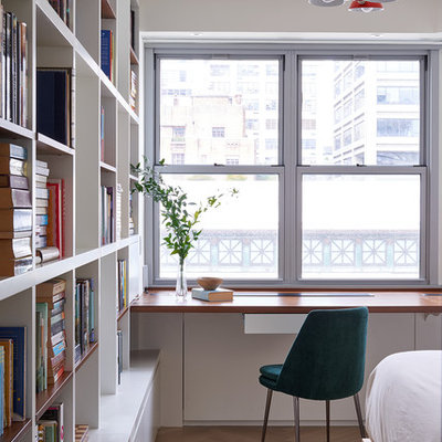 Trendy built-in desk light wood floor and beige floor home office library photo in New York with white walls