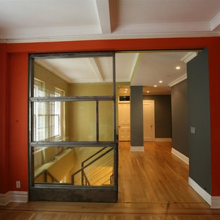 Inspiration for a large industrial study room in New York with orange walls, medium hardwood floors and beige floor.