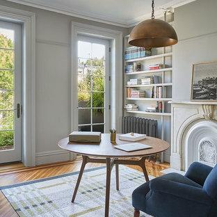 Inspiration för ett stort vintage arbetsrum, med ett bibliotek, grå väggar, ljust trägolv, en standard öppen spis, en spiselkrans i betong, ett fristående skrivbord och brunt golv