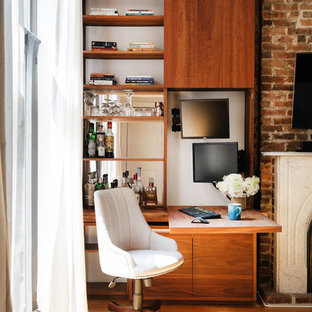 Lantlig inredning av ett litet arbetsrum, med ett inbyggt skrivbord, ljust trägolv, en standard öppen spis och en spiselkrans i tegelsten