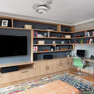 Modern inredning av ett mellanstort hemmabibliotek, med grå väggar, ett inbyggt skrivbord, mellanmörkt trägolv och brunt golv