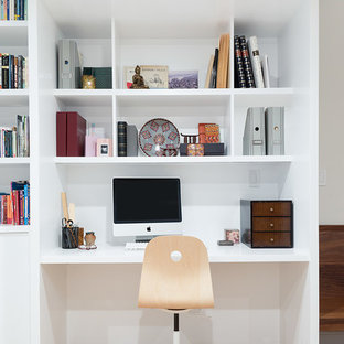 Inspiration for a small transitional built-in desk medium tone wood floor and brown floor study room remodel in New York with white walls