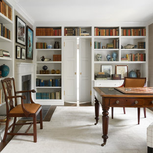 シアトルのトラディショナルスタイルのおしゃれなホームオフィス・仕事部屋 (ライブラリー、標準型暖炉、自立型机) の写真