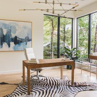 Diseño de despacho moderno, de tamaño medio, sin chimenea, con escritorio independiente, paredes blancas y suelo de madera clara