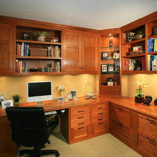 Idee per un grande ufficio stile americano con pareti gialle, moquette e scrivania incassata