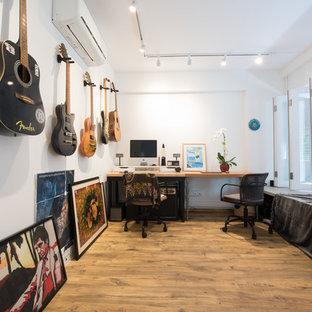 Diseño de estudio bohemio con paredes blancas, suelo de madera clara, escritorio independiente y suelo amarillo