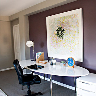This is an example of a large modern study in Los Angeles with purple walls, carpet, no fireplace, a freestanding desk and grey floors.