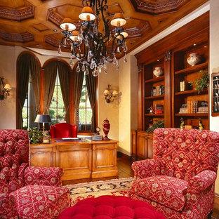 Immagine di un ampio atelier tradizionale con pareti beige, scrivania autoportante e pavimento in legno massello medio