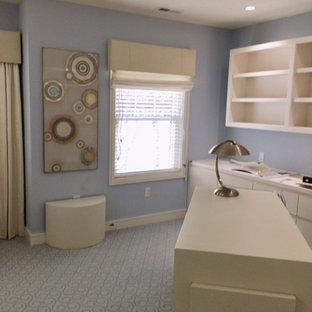 Foto di un grande studio minimalista con libreria, pareti blu, moquette, camino bifacciale, cornice del camino in pietra, scrivania autoportante e pavimento blu