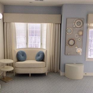 Ispirazione per un grande studio moderno con libreria, pareti blu, moquette, camino bifacciale, cornice del camino in pietra, scrivania autoportante e pavimento blu