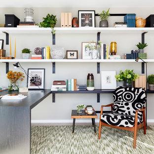 Foto på ett funkis hemmabibliotek, med beige väggar, ett inbyggt skrivbord och beiget golv