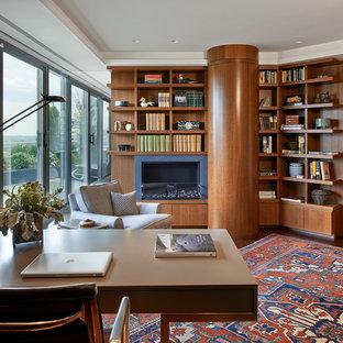 На фото: большое рабочее место в современном стиле с темным паркетным полом, стандартным камином, отдельно стоящим рабочим столом, коричневыми стенами, фасадом камина из металла и коричневым полом