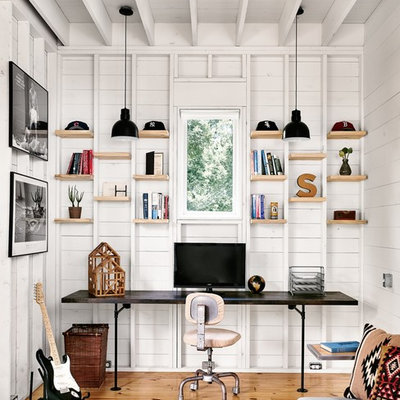 Study room - small cottage built-in desk light wood floor study room idea in Austin with white walls