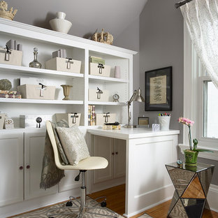 Example of a classic built-in desk medium tone wood floor home office design in Minneapolis with gray walls