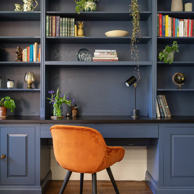 Inspiration for a timeless built-in desk medium tone wood floor and brown floor home office library remodel in Surrey with blue walls