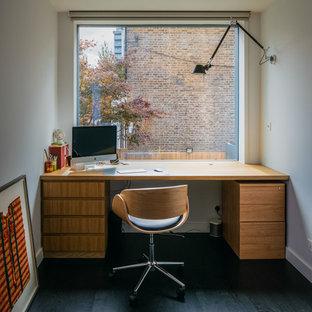 ロンドンのコンテンポラリースタイルのおしゃれな書斎 (白い壁、濃色無垢フローリング、自立型机、黒い床) の写真