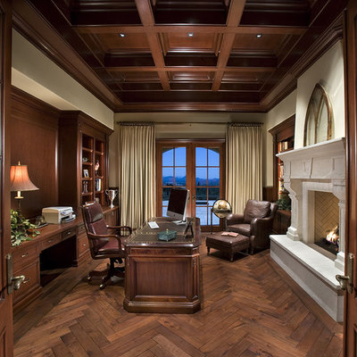 Example of a classic freestanding desk dark wood floor home office design in Los Angeles with beige walls and a standard fireplace