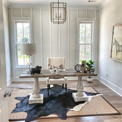 Example of a country freestanding desk medium tone wood floor and brown floor home office design in Atlanta with white walls