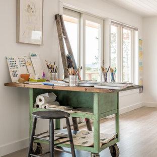 Idee per un atelier stile marinaro con pareti bianche, parquet chiaro, scrivania autoportante e pavimento beige