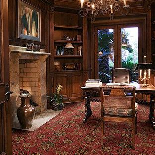 Immagine di uno studio tradizionale di medie dimensioni con moquette, pareti marroni, camino classico, cornice del camino in mattoni e pavimento rosso