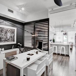 Imagen de despacho actual con paredes negras, suelo de madera en tonos medios y escritorio independiente